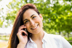 Beautiful brunette in the park making a call Royalty Free Stock Photography