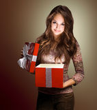Beautiful brunette peeking inside gift box. Stock Images