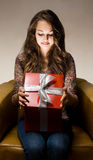 Beautiful brunette peeking inside gift box. Stock Photos