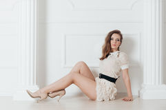 Beautiful brunette with a perfect figure on floor Royalty Free Stock Photos