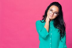 A beautiful brunette on a pink background with glasses touches her neck stock images
