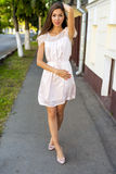 Beautiful brunette pink dress, standing on the street, a bright sunny day, fashion style, urban life, posing, looking Royalty Free Stock Image