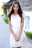 Beautiful brunette pink dress, standing on the street, a bright sunny day, fashion style, urban life, posing, looking Royalty Free Stock Photography