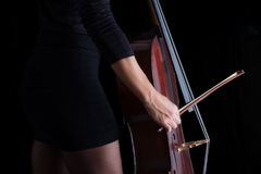 Beautiful brunette playing cello in black dress Stock Photos