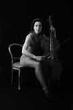 Beautiful brunette playing a cello with selective light in black Royalty Free Stock Photo