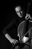 Beautiful brunette playing a cello with selective light in black Royalty Free Stock Photography