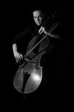 Beautiful brunette playing a cello with selective light in black Stock Image