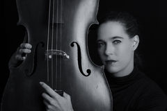 Beautiful brunette playing a cello with selective light in black Royalty Free Stock Photos