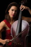 Beautiful brunette playing cello with selective light in red dre Royalty Free Stock Photography