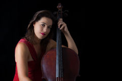 Beautiful brunette playing cello with selective light in red dre Stock Photo