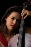 Beautiful brunette playing cello with selective light in red dre Stock Photos