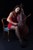 Beautiful brunette playing cello with selective light in red dre Stock Image