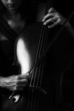 Beautiful brunette playing cello with selective light in red dre Stock Photography