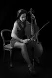 Beautiful brunette playing cello with selective light in red dre Royalty Free Stock Photo
