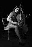 Beautiful brunette playing cello selective light Stock Image