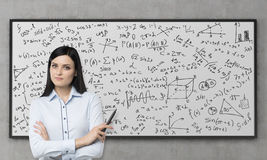 A beautiful brunette is pondering about the solution of complicated analytical problem. Math formulas are written down on the whit Royalty Free Stock Photos