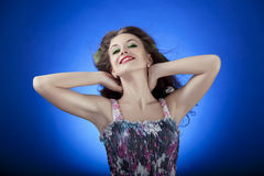 Beautiful brunette posing on blue background, glamour skin, hair Stock Photo
