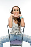 The beautiful brunette posing with a chair Royalty Free Stock Photo