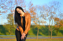 Beautiful brunette  posing at colorful autumn park. Beautiful brunette model woman posing with long wavy hair at colorful autumn park Stock Photo