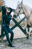 Beautiful brunette posing with a horse in the autumn afternoon at a country ranch. Lifestyle Photo. Fashion photo. Horseback ridin. Beautiful brunette posing Royalty Free Stock Photo