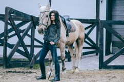 Beautiful brunette posing with a horse in the autumn afternoon at a country ranch. Lifestyle Photo. Fashion photo. Beautiful brunette posing with a horse in the royalty free stock photo
