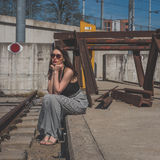 Beautiful brunette posing in an industrial context. Beautiful young brunette with long hair posing along railroad tracks Royalty Free Stock Image