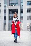 Beautiful brunette posing outdoor. red coat, striped pullover, jeans and fashion sunglasses. bright red lips. Full height Stock Images