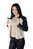 Beautiful brunette posing and showing her leather coat Royalty Free Stock Photos