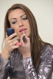 Beautiful brunette putting gloss on her lips Royalty Free Stock Photos