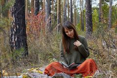 Beautiful brunette is reading a book in an autumn park. royalty free stock photo