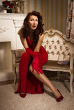 Beautiful brunette in a red dress sitting on the couch Stock Photos