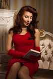 Beautiful brunette in a red dress sitting on the couch Stock Photography