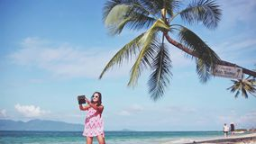 Beautiful brunette in a red dress and sunglasses taking selfie with mobile phone on the sandy beach under the palm trees. Beautiful brunette in a red dress and stock footage