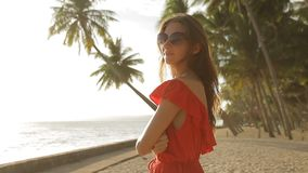 Young woman with tablet computer is walking by the sea and smiling. Beautiful brunette in a red long dress and sunglasses walking by the sea. The girl is using a stock video