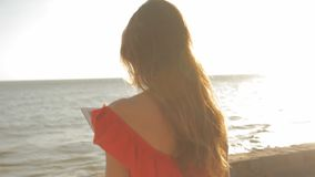 Young woman in a red dress walking on a sunny beach. She is using a tablet and smiling stock video