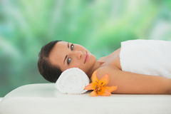 Beautiful brunette relaxing on massage table smiling at camera Stock Photo