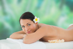 Beautiful brunette relaxing on massage table smiling at camera Stock Photography