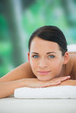 Beautiful brunette relaxing on massage table smiling at camera Stock Image