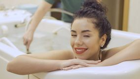 Beautiful brunette relaxing during procedure of hydromassage. Beautiful brunette in bikini lays in the bath in the spa. The doctor makes a hydromassage of body stock footage