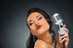 Beautiful brunette with a retro microphone. Portrait of a beautiful brunette with a retro microphone stock photography
