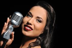 Beautiful brunette with a retro microphone. Portrait of a beautiful brunette with a retro microphone stock photos