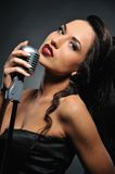 Beautiful brunette with a retro microphone. Portrait of a beautiful brunette with a retro microphone royalty free stock images