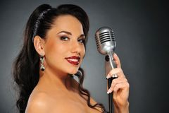Beautiful brunette with a retro microphone. Portrait of a beautiful brunette with a retro microphone royalty free stock image