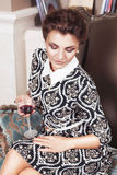 Beautiful brunette rich saucy woman in elegant dress sitting on a chair in a room with classic interior drinking wine Royalty Free Stock Photography