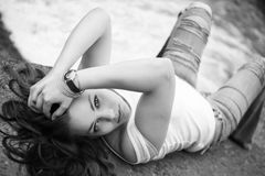 Beautiful brunette at the river. Beautiful brunette in torn jeans  and white shirt lying on the rocks at the river, fashion photography, black and white photo Stock Photography