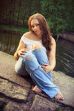 Beautiful brunette at the river. Beautiful brunette in torn jeans  and white shirt sits on the rocks at the river, fashion photography Royalty Free Stock Images