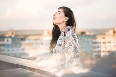 Beautiful brunette on the roof of a house royalty free stock image