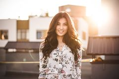Beautiful brunette on the roof of a house stock photo