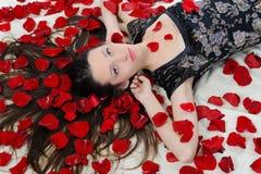 Beautiful brunette in rose petals Stock Image