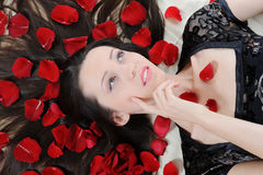 Beautiful brunette in rose petals Stock Photography